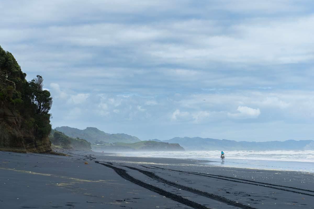 Reiterin am Awakino Beach in Neuseeland