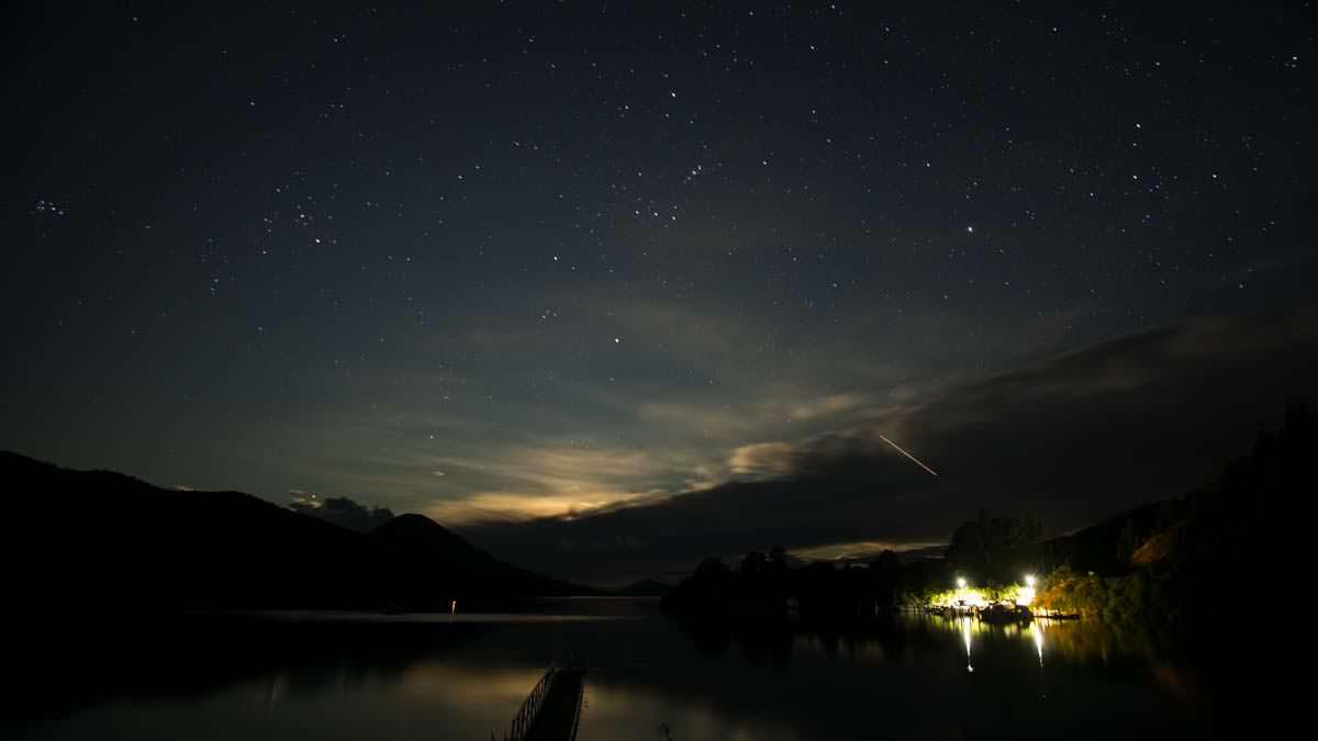 Nachthimmel mit Sternschnuppe über der Elaine Bay, Neuseeland