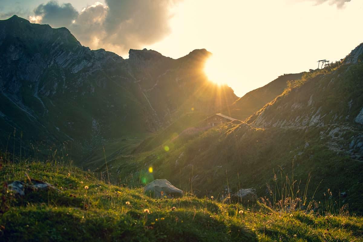 Eine romantische Atmosphäre entfaltet sich, wenn die Sonne über den Almen im Allgäu untergeht
