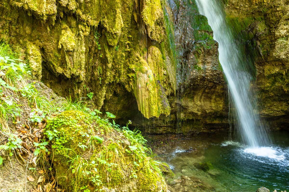Der Hinanger Wasserfall fließt über Kalktuff und Moos in ein türkisgrünes Becken